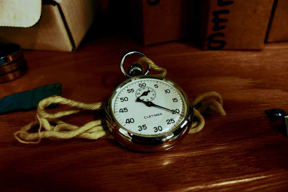 white pocket watch with gold colored frame on brown wooden board