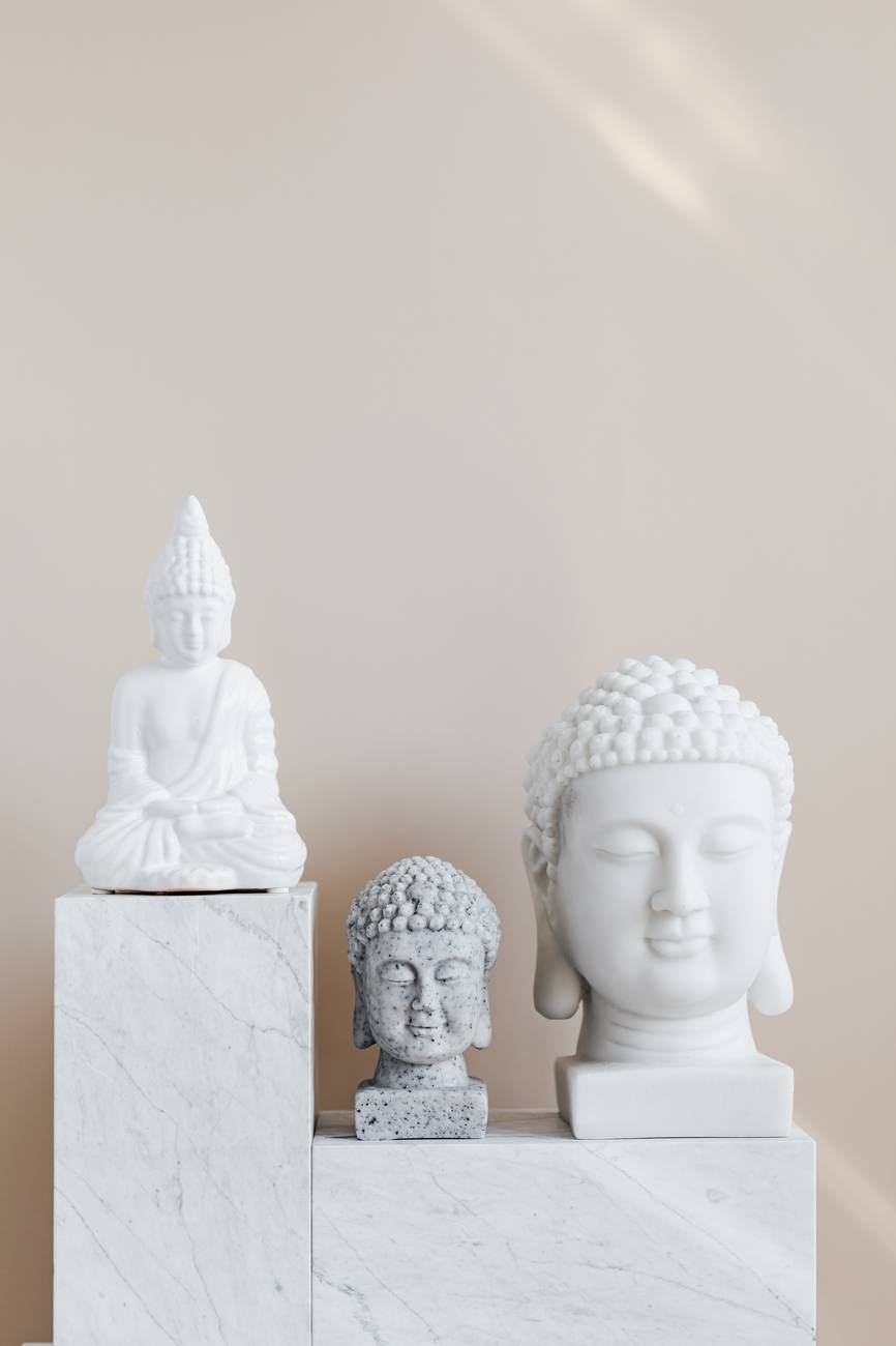 composition of buddha statues on marble stand